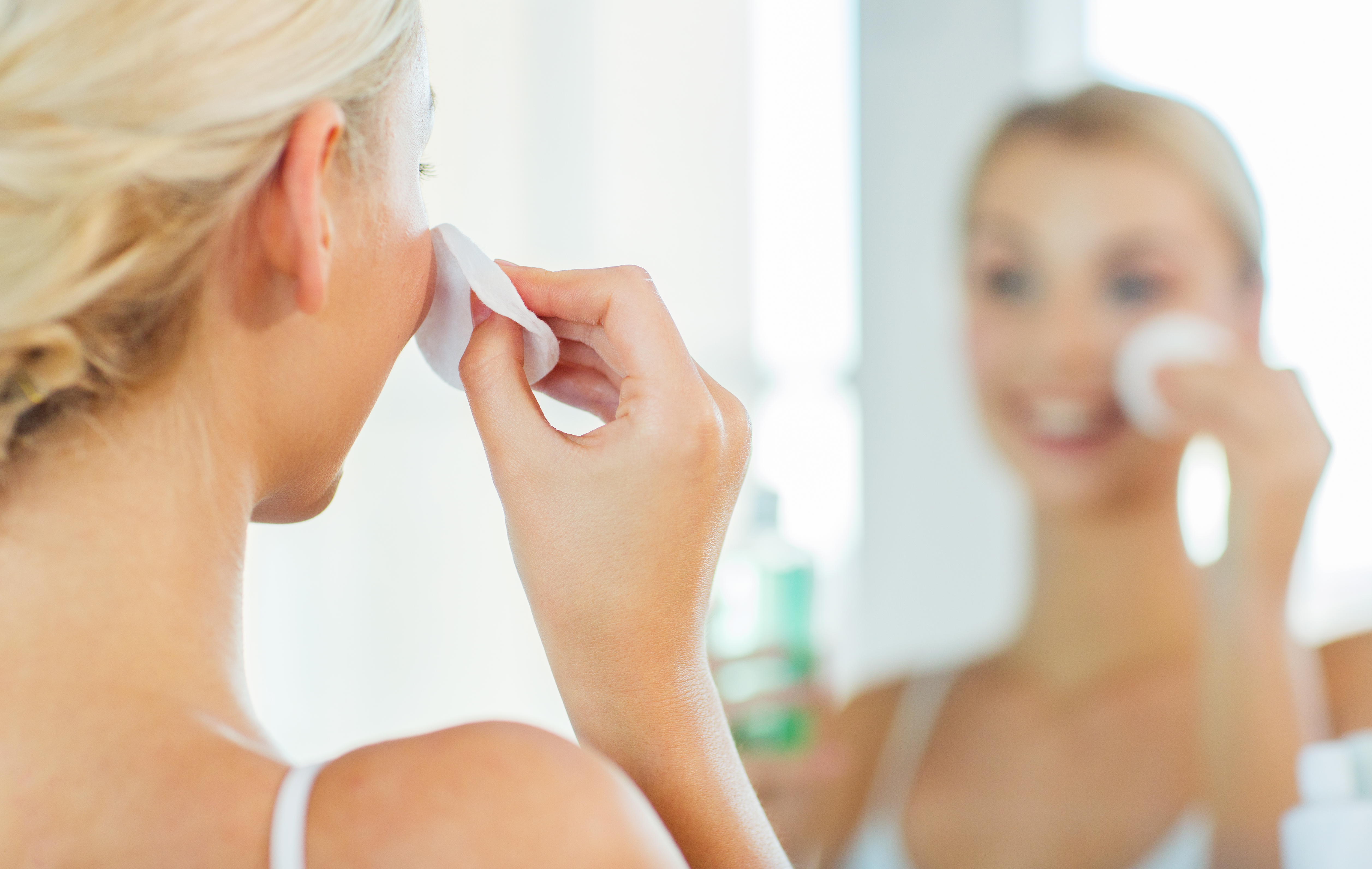 close up of woman cleaning face at bathroom